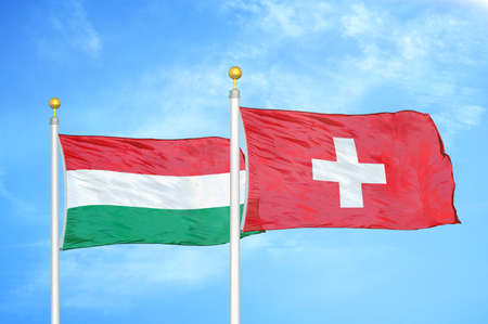 Hungary and Switzerland two flags on flagpoles and blue cloudy sky background