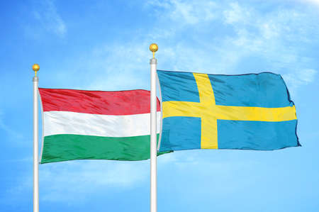 Hungary and Sweden two flags on flagpoles and blue cloudy sky background