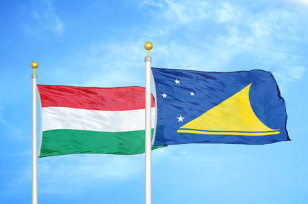 Hungary and Tokelau two flags on flagpoles and blue cloudy sky background