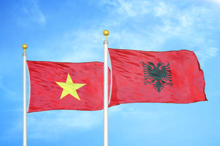Vietnam and Albania two flags on flagpoles and blue cloudy sky background