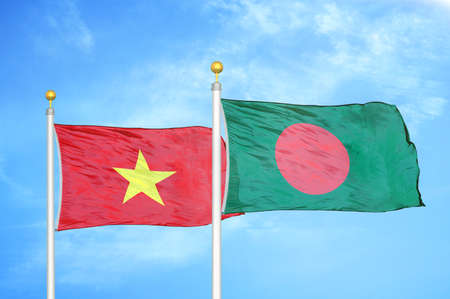 Vietnam and Bangladesh two flags on flagpoles and blue cloudy sky background Stock Photo