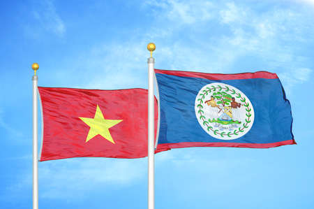 Vietnam and Belize two flags on flagpoles and blue cloudy sky background