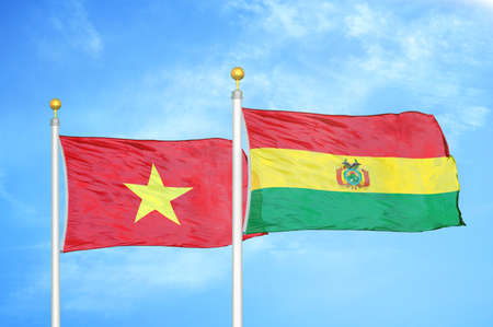Vietnam and Bolivia two flags on flagpoles and blue cloudy sky background