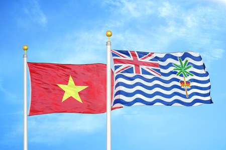Vietnam and British Indian Territory two flags on flagpoles and blue cloudy sky background