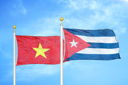 Vietnam and Cuba two flags on flagpoles and blue cloudy sky background