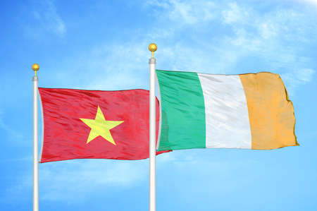 Vietnam and Ireland two flags on flagpoles and blue cloudy sky background