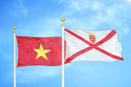 Vietnam and Jersey two flags on flagpoles and blue cloudy sky background