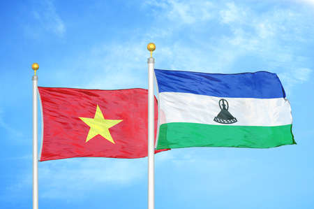 Vietnam and Lesotho two flags on flagpoles and blue cloudy sky background