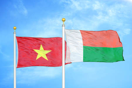 Vietnam and Madagascar two flags on flagpoles and blue cloudy sky background Stock Photo