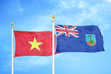 Vietnam and Montserrat two flags on flagpoles and blue cloudy sky background Stock Photo