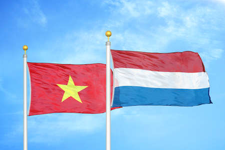 Vietnam and Netherlands two flags on flagpoles and blue cloudy sky background Stock Photo
