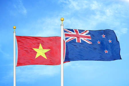 Vietnam and New Zealand two flags on flagpoles and blue cloudy sky background Stock Photo