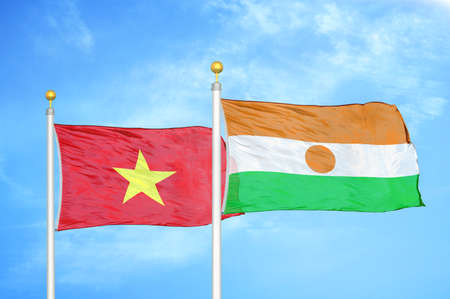 Vietnam and Niger two flags on flagpoles and blue cloudy sky background