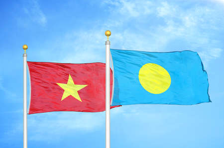 Vietnam and Palau two flags on flagpoles and blue cloudy sky background