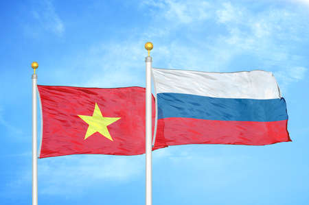 Vietnam and Russia two flags on flagpoles and blue cloudy sky background Stock Photo