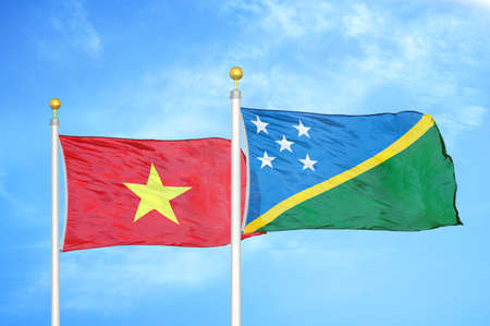 Vietnam and Solomon Islands two flags on flagpoles and blue cloudy sky background