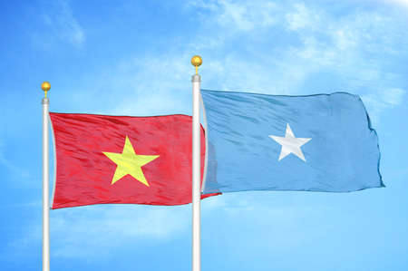 Vietnam and Somalia two flags on flagpoles and blue cloudy sky background