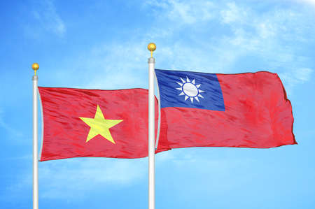 Vietnam and Taiwan two flags on flagpoles and blue cloudy sky background