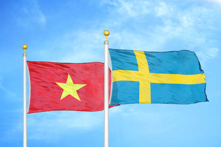 Vietnam and Sweden two flags on flagpoles and blue cloudy sky background Standard-Bild