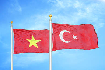 Vietnam and Turkey two flags on flagpoles and blue cloudy sky background