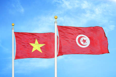 Vietnam and Tunisia two flags on flagpoles and blue cloudy sky background