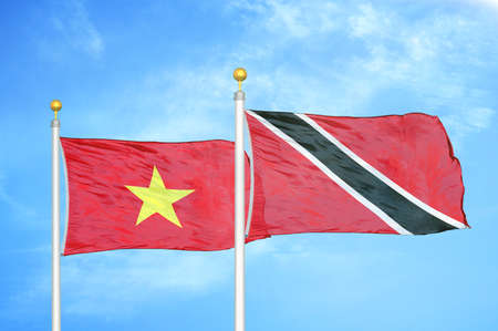Vietnam and Trinidad and Tobago two flags on flagpoles and blue cloudy sky background
