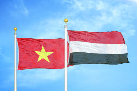 Vietnam and Yemen two flags on flagpoles and blue cloudy sky background Stock Photo