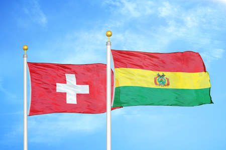 Switzerland and Bolivia two flags on flagpoles and blue cloudy sky background