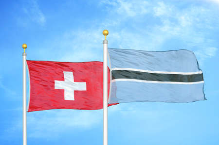Switzerland and Botswana two flags on flagpoles and blue cloudy sky background