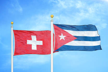 Switzerland and Cuba two flags on flagpoles and blue cloudy sky background