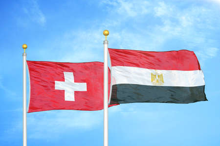 Switzerland and Egypt two flags on flagpoles and blue cloudy sky background