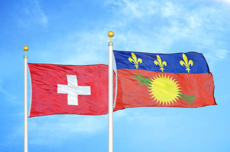 Switzerland and Guadeloupe two flags on flagpoles and blue cloudy sky background