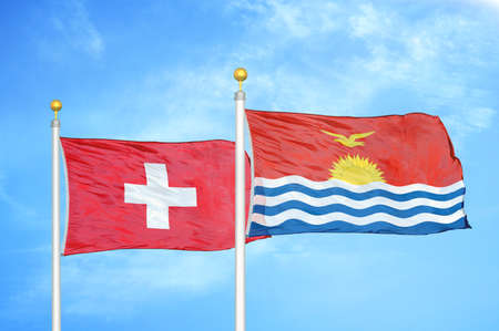 Switzerland and Kiribati two flags on flagpoles and blue cloudy sky background