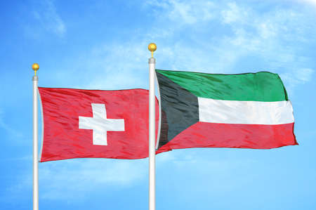 Switzerland and Kuwait two flags on flagpoles and blue cloudy sky background