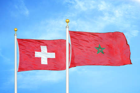 Switzerland and Morocco two flags on flagpoles and blue cloudy sky background