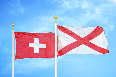 Switzerland and Northern Ireland two flags on flagpoles and blue cloudy sky background Stock Photo
