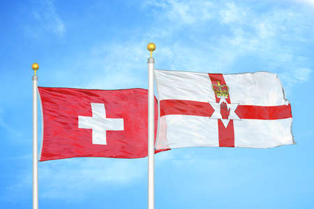 Switzerland and Northern Ireland two flags on flagpoles and blue cloudy sky background