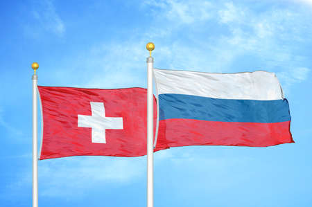 Switzerland and Russia two flags on flagpoles and blue cloudy sky background