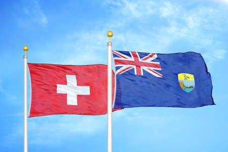 Switzerland and Saint Helena two flags on flagpoles and blue cloudy sky background
