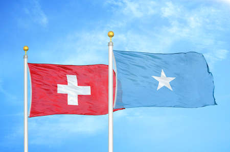 Switzerland and Somalia two flags on flagpoles and blue cloudy sky background