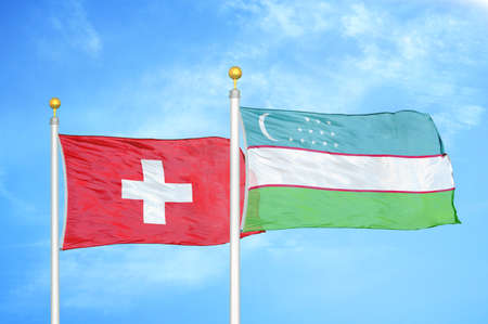 Switzerland and Uzbekistan two flags on flagpoles and blue cloudy sky background