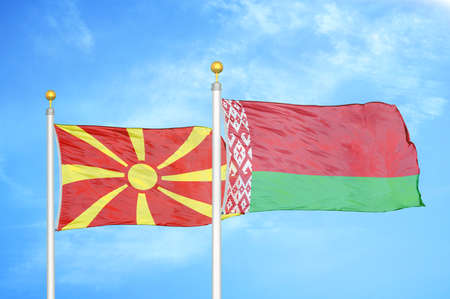 North Macedonia and Belarus two flags on flagpoles and blue cloudy sky background