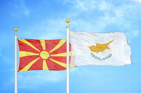 North Macedonia and Cyprus two flags on flagpoles and blue cloudy sky background