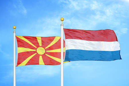 North Macedonia and Netherlands two flags on flagpoles and blue cloudy sky background