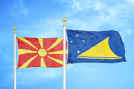 North Macedonia and Tokelau two flags on flagpoles and blue cloudy sky background