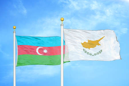 Azerbaijan and Cyprus two flags on flagpoles and blue cloudy sky background