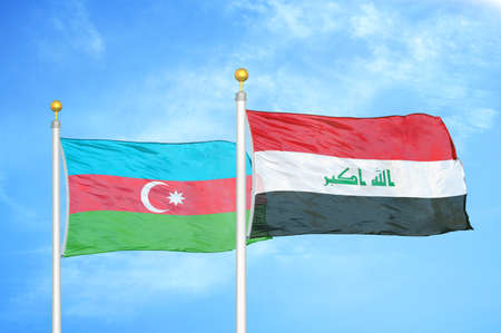 Azerbaijan and Iraq two flags on flagpoles and blue cloudy sky background Reklamní fotografie