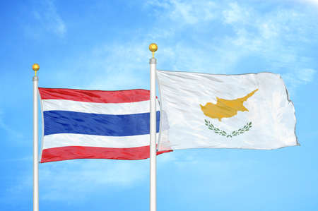 Thailand and Cyprus two flags on flagpoles and blue cloudy sky background Imagens