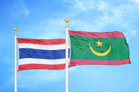 Thailand and Mauritania two flags on flagpoles and blue cloudy sky background