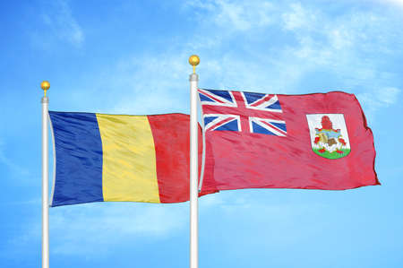 Romania and Bermuda two flags on flagpoles and blue cloudy sky background